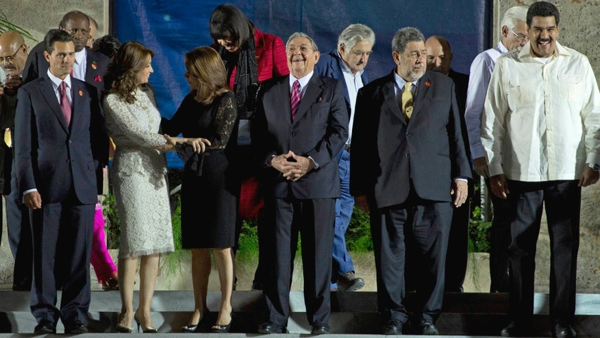 Cuba's President Raul Castro, center, waits for the other dignitaries to find their places for the group photo at the Community of Latin American and Caribbean Countries (CELAC) summit at Revolutionary Palace in Havana, Cuba, Tuesday, Jan. 28, 2014. From left to right, front row, are Mexico's President Enrique Pena Nieto, Mexico's first lady Angelica Rivera, Coata Rica's President Laura Chinchilla, Castro, Uruguay's President Jose Mujica, Prime Minister of Saint Vincent and the Grenadines Ralph Everard Gonsalves and Venezuela's President Nicolas Maduro. (AP Photo/Desmond Boylan)