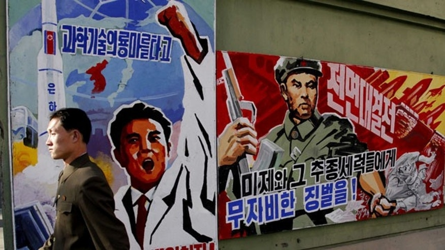 "FILE - In this March 26, 2013 file photo, a North Korean man walks past propaganda posters in Pyongyang, North Korea, that threaten punishment to the ""U.S. imperialists and their allies."" (AP Photo/Kim Kwang Hyon, File)"