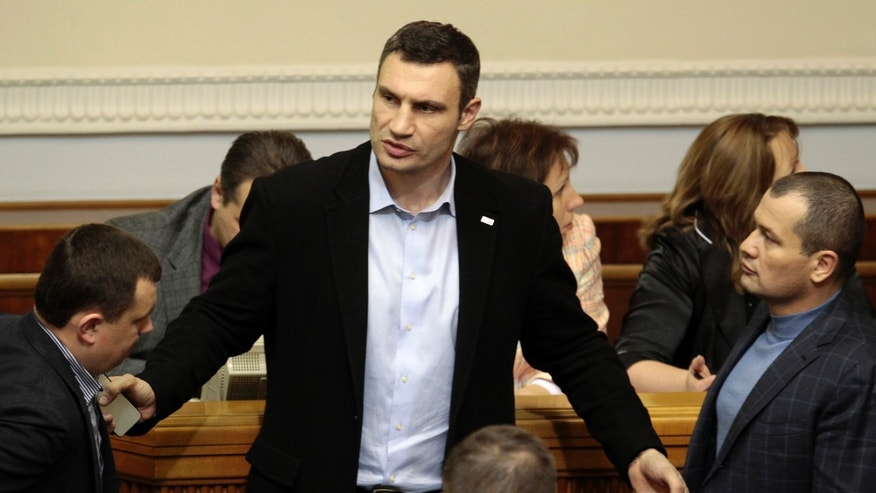 Ukrainian opposition leader and former WBC heavyweight boxing champion Vitali Klitschko, center, talks to lawmakers in the parliament session hall, in Kiev, Ukraine, Tuesday, Jan. 28, 2014. In back-to-back moves to try and resolve Ukraine's political crisis, the prime minister submitted his resignation Tuesday and parliament repealed anti-protest laws that had set off violent clashes between protesters and police. (AP Photo/Sergei Chuzavkov)