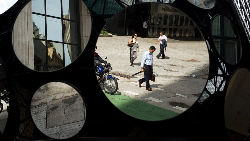 Office workers are reflected in a building's decorative mirrors in downtown Buenos Aires, Argentina, Tuesday, Jan. 28, 2014. The local currency has plunged in value against the U.S. dollar over the last week in Argentina, which has one of the world's highest inflation rates.  (AP Photo/Victor R. Caivano)