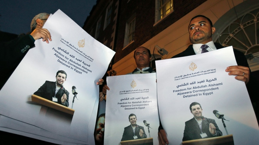 FILE - In this Tuesday, Nov. 12, 2013 file photo, demonstrators hold placards with pictures of Al-Jazeera Arabic network journalist Abdullah Al Shami who along with cameraman Mohamed Badr remain in custody in Egypt, during a protest calling for their release, outside Egypt's embassy in London. Egypt's chief prosecutor has referred 20 journalists who work for the Qatar-based Al-Jazeera network, including four foreigners, to a criminal trial on charges of joining or assisting a terrorist group and spreading false news that endangers national security. Egypt's interim-backed military government accuses the Qatar-based broadcaster of being biased in favor of the Muslim Brotherhood, which authorities have branded a terrorist organization. Only eight are currently in detention. (AP Photo/Lefteris Pitarakis, File)