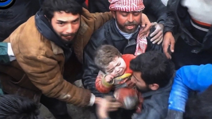In this citizen journalism image made from Wednesday, Jan. 22, 2014 video provided by Nur Media Center, an anti-government activist group, which has been authenticated based on its contents and other AP reporting, one of the men holds 14-month-old Ghina Khalil after they dig her out of rubble in Aleppo, Syria. The chubby toddler was pulled out after men pulled aside rocks, concrete rubble and dust to free her, caught under a smashed building, bombed by the government forces in the area of Masaraniyeh in Aleppo. (AP Photo/Nur Media Center)