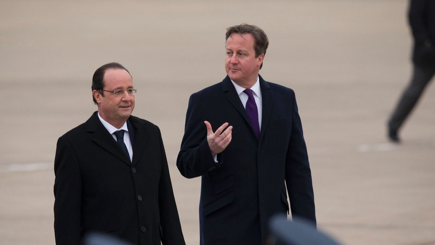 British Prime Minister David Cameron, right, walks with French President Francois Hollande after inspecting an honour guard following Hollande's arrival for their one-day summit at the RAF Brize Norton airbase in Brize Norton, England, Friday, Jan. 31, 2014.  (AP Photo/Matt Dunham)