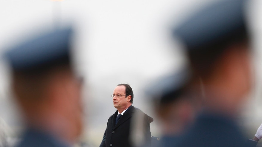 French President Francois Hollande listens to the French national anthem before reviewing an honour guard after his arrival for a one-day summit at the RAF Brize Norton airbase in Brize Norton, England, Friday, Jan. 31, 2014.  (AP Photo/Andrew Winning, Pool)