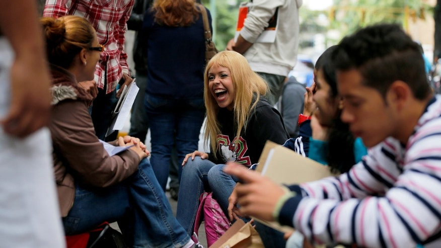 "In this Jan. 28, 2014 photo, Daniela Rodriguez laughs with friends as she waits outside Ireland's consulate in Caracas, Venezuela. Venezuela's best and brightest are abandoning their homeland in droves. ""I'll blindly go anywhere,"" said Rodriguez, who has been unable to find work as a journalist since graduating college in 2010, so instead works as a sales clerk at a clothing store. (AP Photo/Fernando Llano)"