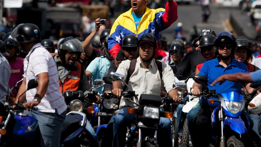 Aury Carrasquel, leader of a group of motocyclists from the Chacao municipality, shouts slogans against a proposed nighttime curfew for two-wheelers as he rides in a protest by motorcyclists in Caracas, Venezuela, Friday, Jan. 31, 2014. President Nicolas Maduro's government this month lent its support to proposals to ban motorcycles from circulating at night, arguing that the vehicles are used to carry out murders and kidnappings that have proliferated recently. (AP Photo/Alejandro Cegarra)