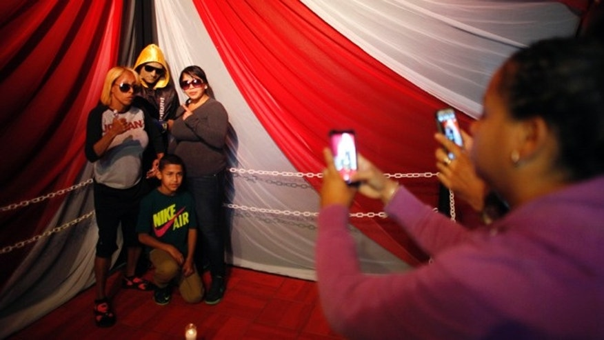 Jan. 31: Lidianette Carmona, behind right, the wife of the late boxer Christopher Rivera, stands with Rivera's family as they pose for photos taken by fans with Rivera's body propped up in a fake boxing ring during his wake at the community recreation center within the public housing project where he lived in San Juan, Puerto Rico.