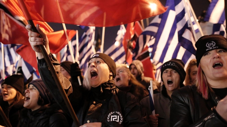 Supporters of Greece's extreme right party Golden Dawn shout slogans during a rally in Athens on Saturday, Feb.1, 2014. About 3,000 people took part in the rally to commemorate a 1996 incident which cost the lives of three navy officers and brought Greece and Turkey to the brink of war. A number of leftist groups held two separate counter-rallies a short distance away, but police forbade the groups from marching and meeting each other to prevent violent incidents. Six lawmakers of the party, including the Golden Dawn's leader Nikolaos Michaloliakos, are in jail on charges of being prominent members of a criminal organization. (AP Photo/Yannis Kolesidis)