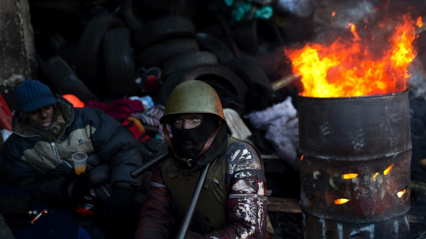 An opposition supporter looks on as he warms himself next to a fire in a barricade near Kiev's Independence Square, the epicenter of the country's current unrest, Ukraine, Friday, Jan. 31, 2014. Ukraine's embattled president Viktor Yanukovych is taking sick leave as the country's political crisis continues without signs of resolution. (AP Photo/Emilio Morenatti)