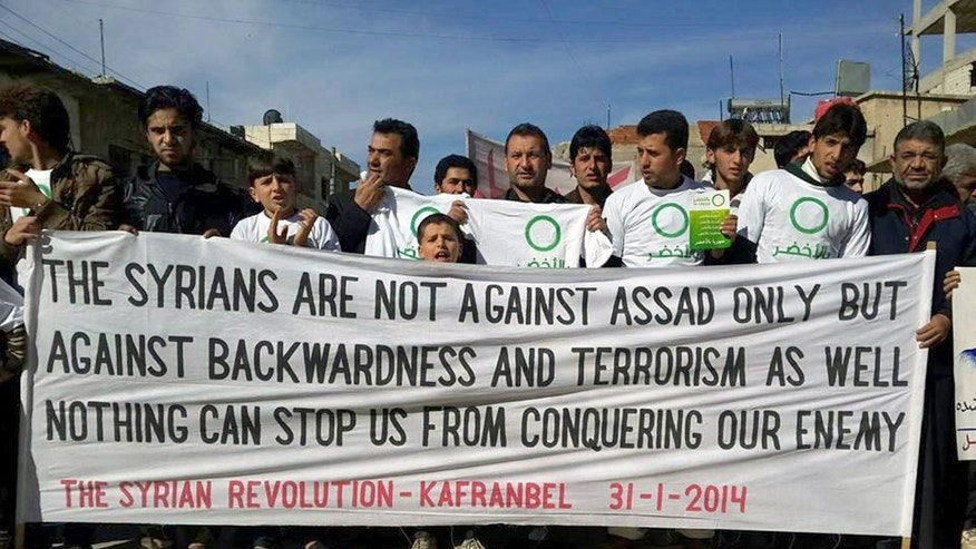 In this image provided by Edlib News Network (ENN), an anti-Bashar Assad activist group, which has been authenticated based on its contents and other AP reporting, anti-Syrian government protesters hold a banner during a demonstration at Kafr Nabil town in Idlib province, northern Syria, Friday, Jan. 31, 2014. (AP Photo/Edlib News Network ENN)