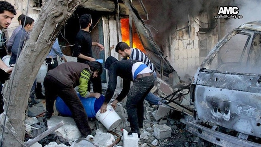 Feb. 1, 2014: In this citizen journalism image provided by Aleppo Media Center (AMC), an anti-Bashar Assad activist group, and authenticated based on its contents and other AP reporting, Syrian citizens fill water in a bucket to extinguish shops in flames caused by a Syrian government forces warplane attack, at al-Bab neighborhood in Aleppo, Syria.