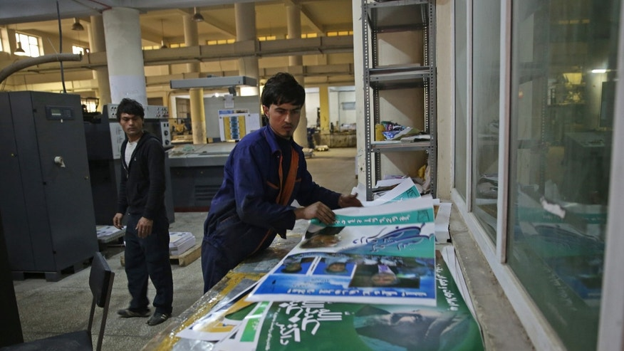 Afghan employees prepare printed posters of presidential election candidates at Baheer Printing Company a day before Afghanistan's presidential election campaign officially kicks off, in Kabul, Afghanistan, Saturday, Feb. 1, 2014. The posters are printed. The rallies are organized. A televised debate is planned. Campaign season for Afghanistan's presidential election kicks off Sunday, and the stakes are high for the 11 candidates vying to succeed President Hamid Karzai and oversee the final chapter in a NATO-led combat mission. (AP Photo/Massoud Hossaini)