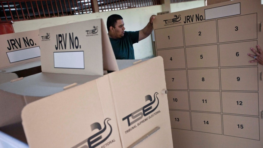 A worker from the Electoral Supreme Tribune (TSE) prepares a polling station for the presidential election in San Salvador, El Salvador, Saturday, Feb. 1, 2014. El Salvador will hold its presidential election on Sunday. (AP Photo/Esteban Felix)