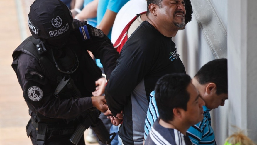 An alleged member of the Mara Salvatrucha gang is handcuffed by a policeman of the anti-gang unit while lined-up against a wall next to other suspects during a police raid in San Salvador, El Salvador, Friday, Jan. 31, 2014. Despite a drop in killings in the country where an average of 14 people a day were killed before a 2012 truce, violence is still one of the main issues in Sunday's presidential election. (AP Photo/Esteban Felix)