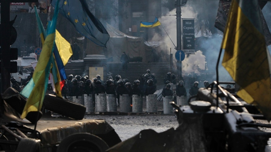 Riot police line up as seen through protesters' barricades in central Kiev, Ukraine, Saturday, Feb. 1, 2014. Ukraine's embattled president Viktor Yanukovych is taking sick leave as the country's political crisis continues without signs of resolution. (AP Photo/Sergei Chuzavkov)