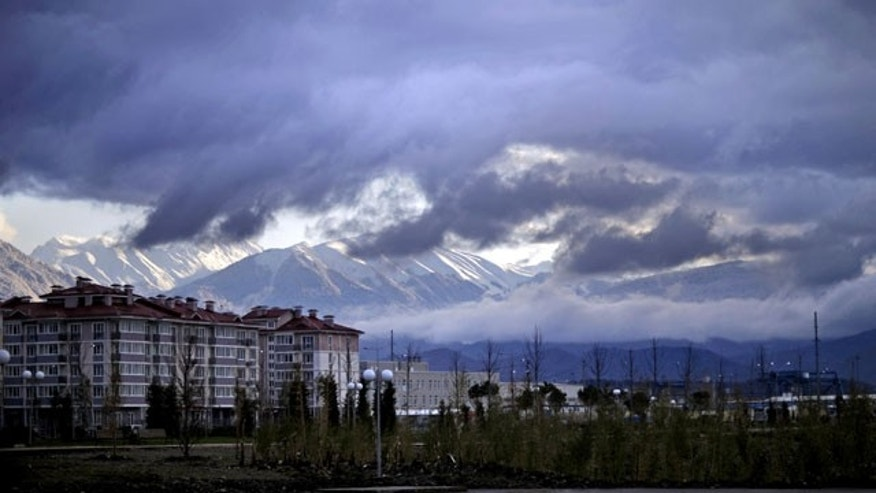 February 1, 2014: The Caucasus Mountains, site of the 2014 Winter Olympic outdoor snow sport and sliding track events, rise above a recently built housing complex, at left, near the Olympic Park by the Black Sea in the Coastal Cluster in Sochi, Russia. (AP Photo/David Goldman)