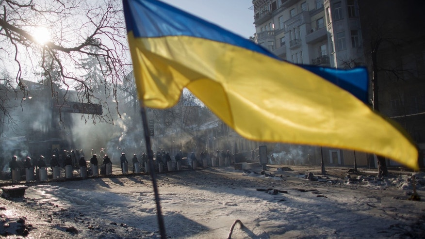 A Ukrainian flag flies at a barricade set up by anti-government protesters as riot police stand guard in central Kiev, Ukraine, Sunday, Feb. 2, 2014. Kitted out in masks, helmets and protective gear on the arms and legs, radical activists are the wild card of the Ukraine protests now starting their third month, declaring they're ready to resume violence if the stalemate persists. (AP Photo/Darko Bandic)