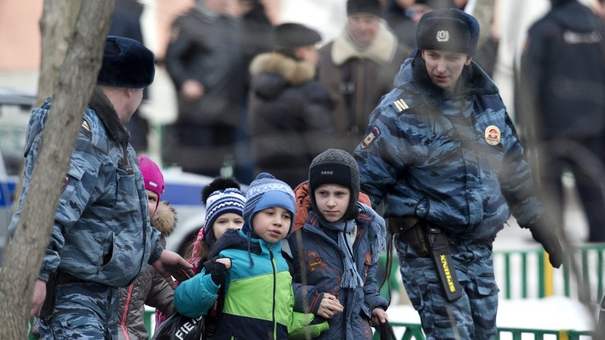 Feb. 3, 2014 - Police officers evacuate children from a Moscow school. An armed teenager burst into the school and killed a teacher and policeman before being taken into custody, investigators said. None of the children who were in school were hurt.