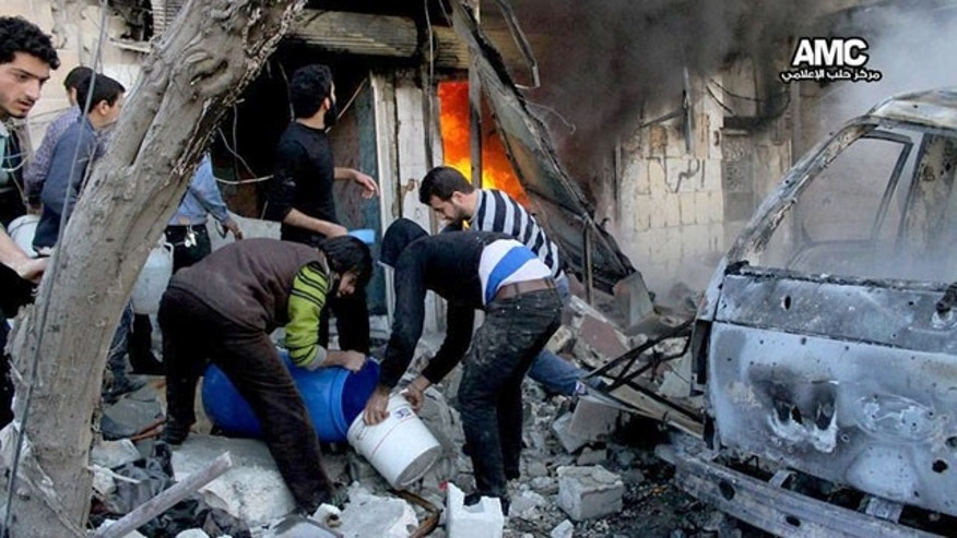 February 1, 2014: In this citizen journalism image provided by Aleppo Media Center (AMC), an anti-Bashar Assad activist group, and authenticated based on its contents and other AP reporting, Syrian citizens fill water in a bucket to extinguish shops in flames caused by a Syrian government forces warplane attack, at al-Bab neighborhood in Aleppo. (AP)