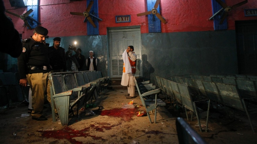 Pakistani police officers examine the site of an explosion inside a cinema hall in Peshawar, Pakistan, Sunday, Feb. 2, 2014. Two blasts ripped through a crowded cinema hall in the northwestern city of Peshawar, killing several people and injuring dozens. Police said two hand grenades were hurled inside the cinema by unknown attackers, local media reported. (AP Photo/Mohammad Sajjad)