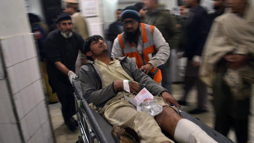 An injured victim of explosion is brought to a  local hospital for treatment in Peshawar, Pakistan, Sunday, Feb. 2, 2014.  Two blasts ripped through a crowded cinema hall in the northwestern city of Peshawar, killing several people and injuring dozens. Police said two hand grenades were hurled inside the cinema by unknown attackers, local media reported. (AP Photo/Mohammad Sajjad)