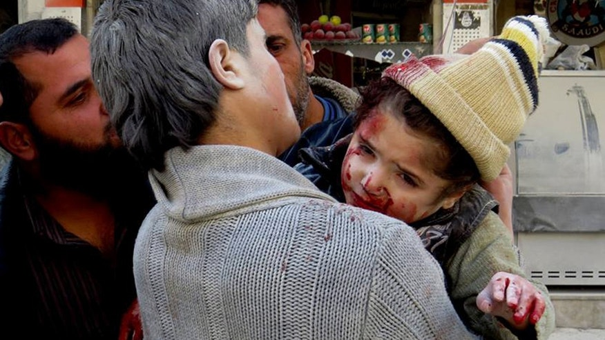 This photo provided by the anti-government activist group Aleppo Media Center (AMC), which has been authenticated based on its contents and other AP reporting, shows a Syrian man carrying a wounded child following a Syrian government airstrike in Aleppo, Syria, Monday, Feb. 3, 2014. Syrian government helicopters and warplanes unleashed a wave of airstrikes on more than a dozen opposition-held neighborhoods in the northern city of Aleppo on Sunday, firing missiles and dropping crude barrel bombs in a ferocious attack that killed at least 36 people, including children, activists said. (AP Photo/Aleppo Media Center, AMC)