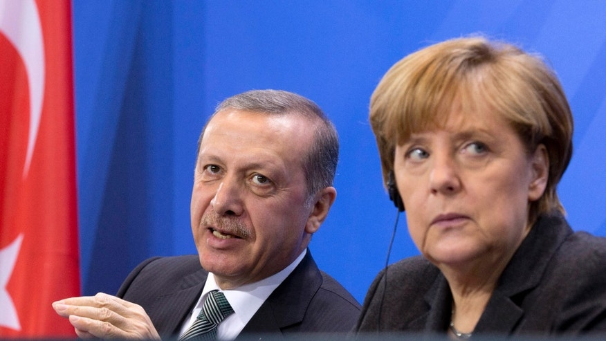 German Chancellor Angela Merkel, right,  listens  as Turkey's Prime Minister Recep Tayyip Erdogan, left,  speaks  during a joint press conference after a meeting at the chancellery in Berlin, Germany, Tuesday, Feb. 4, 2014.  (AP Photo/Axel Schmidt)