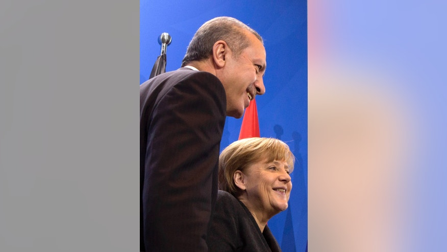 German Chancellor Angela Merkel, right, and Turkey's Prime Minister Recep Tayyip Erdogan, left,  leave   a joint press conference after a meeting at the chancellery in Berlin, Germany, Tuesday, Feb.  4, 2014. (AP Photo/Axel Schmidt)