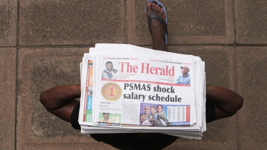 A newspaper vendor carries newspapers for sale with a headline detailing a shocking salary schedule  for top executives at a Medical aid society in Harare, Tuesday, February, 4, 2014. It is the talk of the town: directors across Zimbabwe's public sector are on the take, allegedly awarding themselves huge salaries while most people struggle to get by in an economy on the edge. Last year, Transparency International ranked Zimbabwe at 157 out of 175 countries and territories on a scale rating perceptions of public sector corruption. (AP Photo/Tsvangirayi Mukwazhi)
