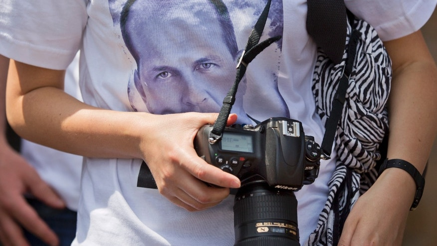 A photojournalist wears a tee-shirt showing the face of detained Al-Jazeera journalist Peter Greste at a demonstration by Kenyan and Nairobi-based foreign media calling for the release of Greste and his colleagues, outside the Egyptian embassy in Nairobi, Kenya Tuesday, Feb. 4, 2014. Nairobi-based correspondent Greste was taken into custody in Egypt on Dec. 29 and is among 20 journalists working for Al-Jazeera, including four foreigners, who will face trial there on charges of joining or aiding a terrorist group and endangering national security - an escalation that raised fears of a crackdown on freedom of the press. (AP Photo/Ben Curtis)