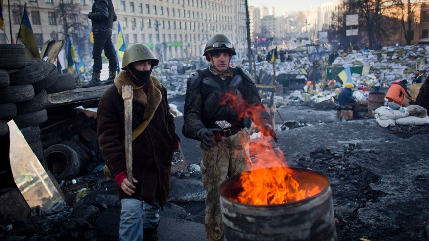 Anti-government protesters warm themselves as they man a barricade in central Kiev, Ukraine, Tuesday, Feb. 4, 2014. Leaders of the anti-government protests that have gripped Ukraine's capital for more than two months say they will seek constitutional changes that will weaken the president's powers. (AP Photo/Darko Bandic)