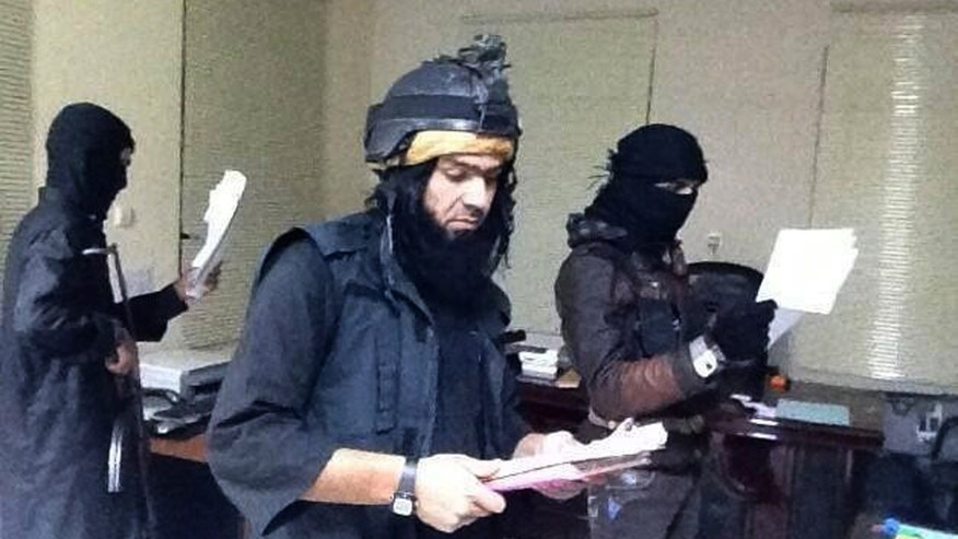 "FILE - This undated file image posted on a militant website on Jan. 4, 2014, which is consistent with other AP reporting, shows Shakir Waheib, center, a leader in the al-Qaida-linked Islamic State of Iraq and the Levant (ISIL), searching a government office in Ramadi, Anbar Province, Iraq. The  ISIL led by Abu Bakr al-Baghdadi is the main driver of destabilizing violence in Iraq and until recently was the main al-Qaida affiliate there. Al-Qaida's general command formally disavowed the group this week, saying it ""is not responsible for its actions."" (AP Photo via militant website, File)"