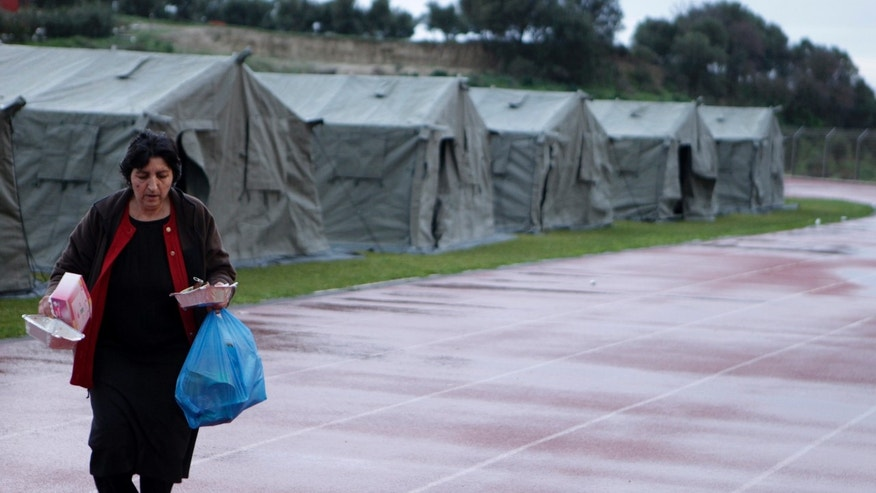 Feb. 4, 2014: A woman carries food in front of tents at a local soccer stadium after Monday's strong earthquake with a preliminary magnitude between 5.7 and 6.1, in Lixouri, on the island of Kefalonia, western Greece.