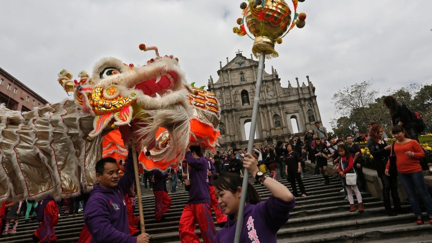 In this Feb. 1, 2014 photo, local artists perform dragon at the famous tourist spot the Ruins of St. Paul's during a Chinese New Year celebration in Macau. This year marks the year of the horse in the Chinese calendar. The annual holiday is the busiest time of year for the former Portuguese colony, which became a special Chinese region in 1999. Many of the millions of mainland Chinese on the move during the holiday, often referred to as the world's biggest migration, head to Macau during the festival. (AP Photo/Vincent Yu)