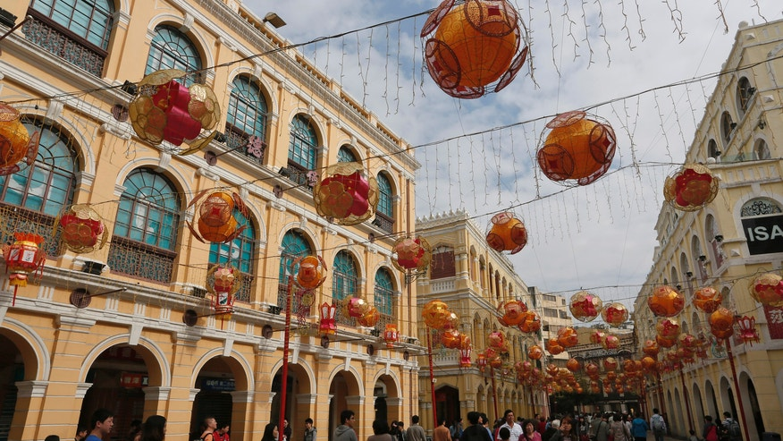 In this Feb. 1, 2014 photo, mainland Chinese tourists walk at the famous tourist spot Senado Square during a Chinese New Year celebration in Macau. The annual holiday is the busiest time of year for the former Portuguese colony, which became a special Chinese region in 1999. Many of the millions of mainland Chinese on the move during the holiday, often referred to as the world's biggest migration, head to Macau during the festival. (AP Photo/Vincent Yu)