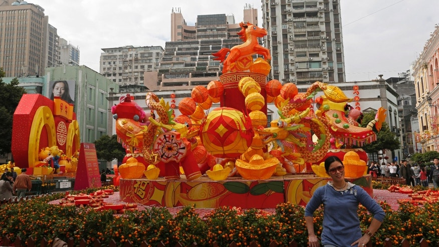 In this Feb. 1, 2014 photo, a mainland Chinese tourist poses for a picture next to decorations during a Chinese New Year celebration in Macau.  The annual holiday is the busiest time of year for the former Portuguese colony, which became a special Chinese region in 1999. Many of the millions of mainland Chinese on the move during the holiday, often referred to as the world's biggest migration, head to Macau during the festival. (AP Photo/Vincent Yu)