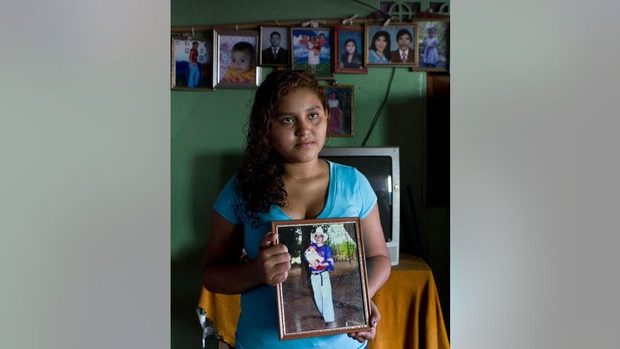 Fatima Alvarenga, the daughter of Jose Salvador Alvarenga, poses for a portrait holding a photograph of herself held by her father when she was a baby, at her family's home in the village of Garita Palmera, El Salvador, Tuesday, Feb. 4, 2014. The account of her father's survival after more than 13 months in an open boat has proven a double miracle for his family, who lost touch with him years ago and thought he was dead. Jose Salvador Alvarenga said he left Mexico in December 2012 for a day of shark fishing and ended up on the remote Marshall Islands. (AP Photo/Esteban Felix)