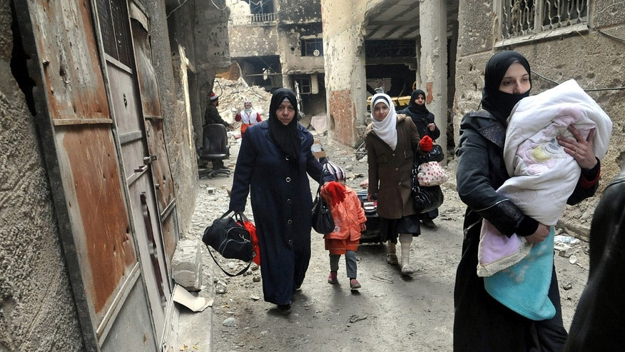 In this photo released by the Syrian official news agency SANA, residents of the besieged Yarmouk Palestinian refugee camp carry their belongings as they flee the camp, on the southern edge of the Syrian capital Damascus, Syria, Tuesday, Feb. 4, 2014. Over the past six days the U.N. continued to distribute food parcels in the Palestinian camp where activists say at least 85 people have died as a result of lack of food and medicine since mid-2013. (AP Photo/SANA)