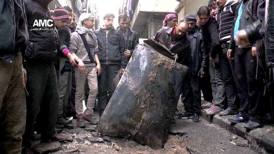 FILE - In this Sunday, Jan. 19, 2014, file photo provided by Aleppo Media Center (AMC), an anti-Bashar Assad activist group, which has been authenticated based on its contents and other AP reporting, Syrian citizens inspect an unexploded barrel of explosives which was dropped from a Syrian forces helicopter, on a street in Aleppo, Syria. For nearly two months, the Syrian government has conducted an intense air campaign on opposition-held districts of the northern city of Aleppo. Airstrikes on the city over the past week alone have killed some 245 people, according to activists. That pace rivals a two-week stretch in the second half of December when more than 500 people were killed in Aleppo airstrikes. (AP Photo/Aleppo Media Center, AMC, File)
