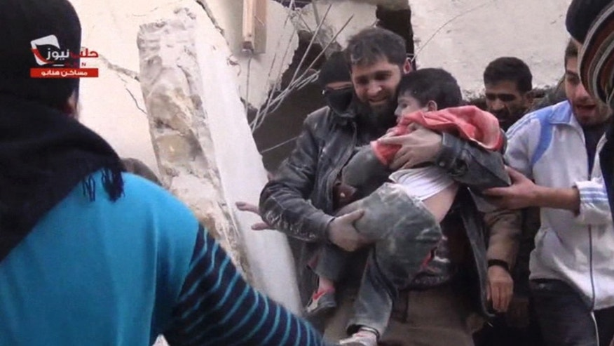 In this image taken from video obtained from the Aleppo News Network, which has been authenticated based on its contents and other AP reporting, a man carries a boy out of a collapsed building that activists said was damaged after a barrel bomb was dropped in Aleppo, Syria, Thursday, Feb. 6, 2014. Syrian rebels launched a new push in the northern province of Aleppo on Thursday to capture key symbols of the government and stormed a major section of a prison there, freeing hundreds of prisoners in the process, activists said. The advance came amid a relentless air campaign by government forces in Aleppo. (AP Photo/Aleppo News Network)