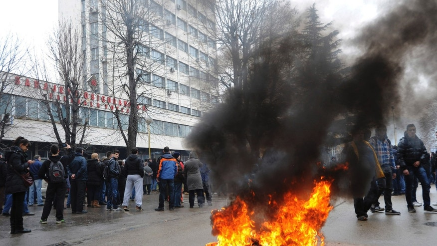 A tyre burns in the street as protesters stoned a local government building in the Bosnian town of Tuzla, 140 kms north of Sarajevo, Thursday, Feb. 6, 2014. Several hundred protesters clashed with police as they tried to storm into the building of the local government and confront the officials there whom they blame for allowing the city's major state-owned companies to go bankrupt after dubious privatizations. The four former state-owned companies that employed most of Tuzla's population were sold but the contracts obliged the new owners to invest in them and make them profitable. But those just sold the assets, stopped paying workers, and filed for bankruptcy. The authorities did nothing about such violation of sales contracts.(AP Photo/Darko Zabus)