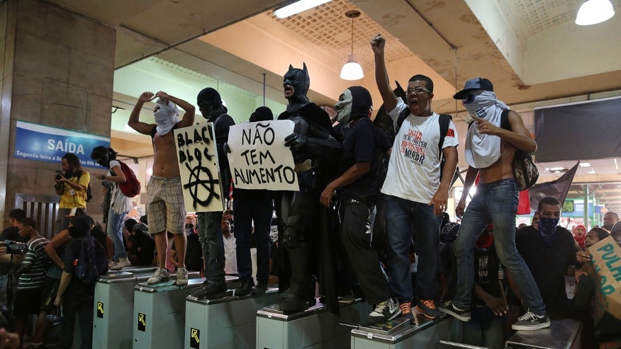 Protesters invade the central train station in protest against the increase of bus fares in Rio de Janeiro, Brazil, Thursday, Feb. 6, 2014. Last year, millions of people took to the streets across Brazil complaining of higher bus fares, poor public services and corruption while the country spends billions on the World Cup, which is scheduled to start in June. (AP Photo/Leo Correa)