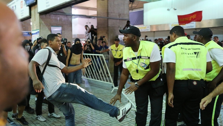 A demonstrators kicks a security guard during a protest against the increase of bus fares in Rio de Janeiro, Brazil, Thursday, Feb. 6, 2014. Last year, millions of people took to the streets across Brazil complaining of higher bus fares, poor public services and corruption, while the country spends billions on the World Cup, which is scheduled to start in June. (AP Photo/Leo Correa)