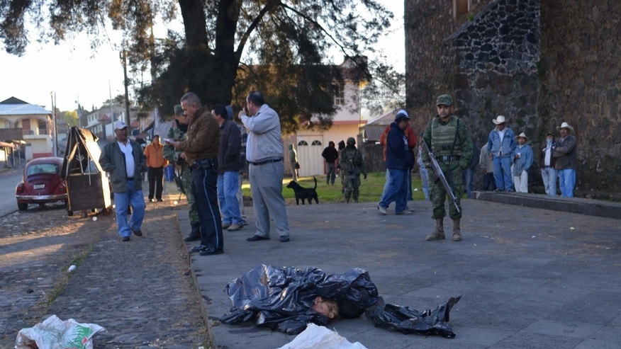 EDS NOTE GRAPHIC CONTENT - Investigators and army soldiers stand near the entrance of a church where four human heads were dumped in the town of Zacan, state of Michoacan, Mexico, Thursday, Feb. 6, 2014. Officials say the remains belong to four men between the ages of 22 and 55 years of age. Mexico's federal government in recent weeks has sent thousands of soldiers and federal police after self-defense groups organized to battle with the Knights Templar drug cartel. (AP Photo/Agencia Esquema)