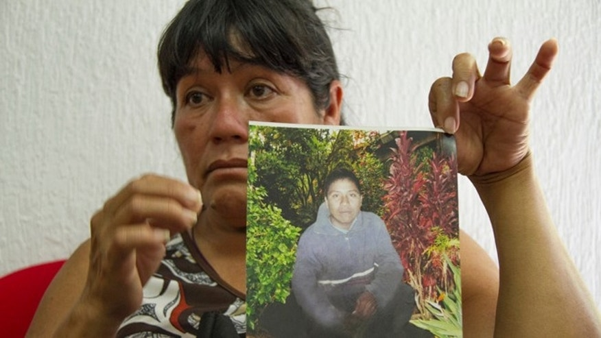 Maria Rios Cueto, holds up a photo of her nephew, Ezequiel Cordoba Rios in Tuxtla Gutierrez, Mexico, Thursday Feb. 6, 2014.