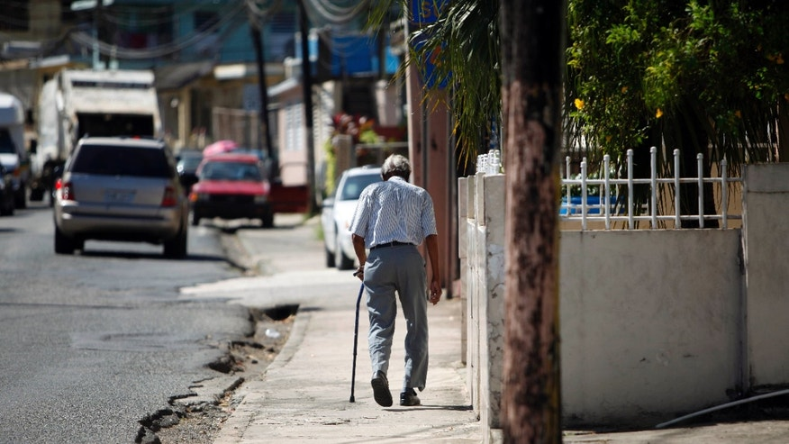 In this Nov. 14, 2013 photo, Mariano Perez Morales, 75, walks a sidewalk in Barceloneta, Puerto Rico. Retirees are struggling with rising water, power and other utility prices, which the government hiked to trim a budget deficit projected to hit $820 million this year. The weak economy also has reduced pensions for retired Puerto Rican public workers. (AP Photo/Ricardo Arduengo)