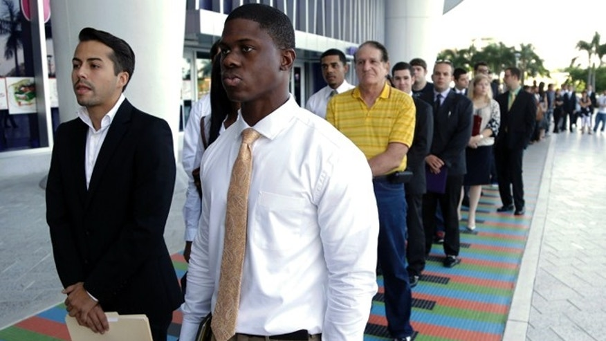 FILE - In this Wednesday, Oct. 23, 2013, file photo, Luis Mendez, 23, left, and Maurice Mike, 23, wait in line at a job fair held by the Miami Marlins, at Marlins Park in Miami. Employers added a scant 74,000 jobs in December after averaging 214,000 in the previous four months. The Labor Department said Friday, Jan. 10, 2014, that the unemployment rate fell from 7 percent in November to 6.7 percent, its lowest level since October 2008. But the drop occurred mostly because many Americans stopped looking for jobs. Once people without jobs stop looking for one, the government no longer counts them as unemployed. (AP Photo/Lynne Sladky, File)