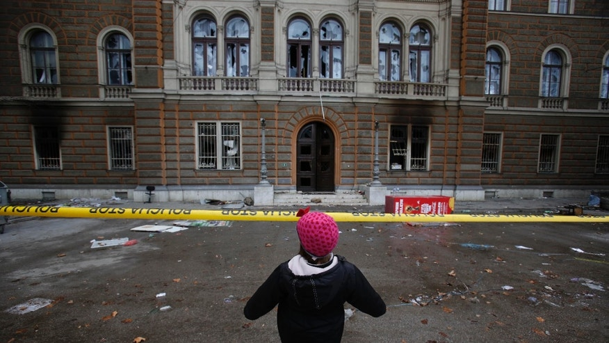 A young Bosnian girl plays in front of the burnt building of the Bosnian Presidency in Sarajevo on Saturday, Feb. 8, 2014. Anti-government protesters have stormed into the Bosnian presidency and another government building in Sarajevo and set them ablaze as riot police fired tear gas in a desperate attempt to stop them. Smoke rose from several cities as thousands vented their fury over the Balkan nation's high unemployment and rampant corruption. (AP Photo/Amel Emric)