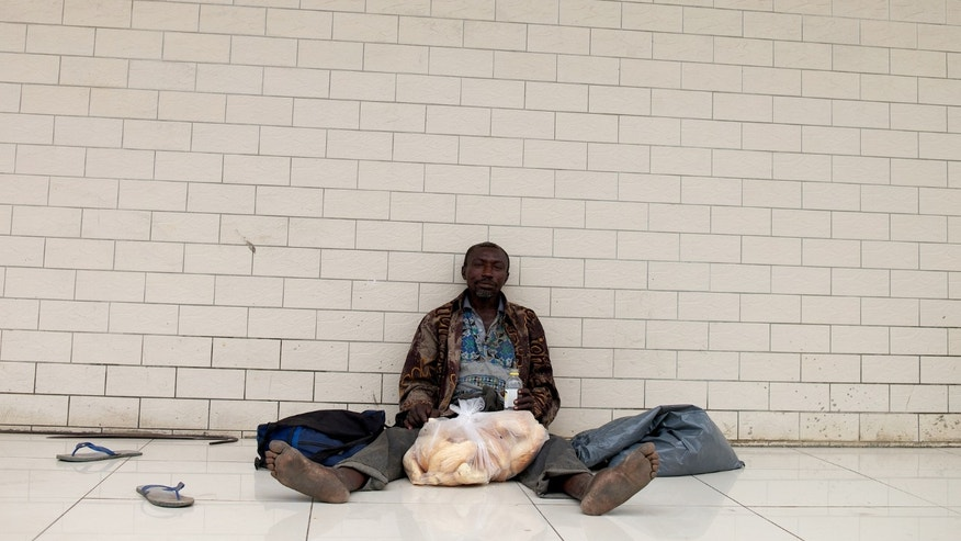 In this Jan. 22, 2014 photo, a homeless man sits with bags of bread given to him by a store as he sits outside a Chinese market in Paramaribo, Suriname. Unsolved murders of a dozen homeless people over the past eight years haunt the nighttime streets of Suriname's capital, and baffle the nation's police force. Deborah Winson, who manages the government's homeless bureau, said that roughly 200 people sleep on Paramaribo's streets each night. (AP Photo/Ertugrul Kilic)
