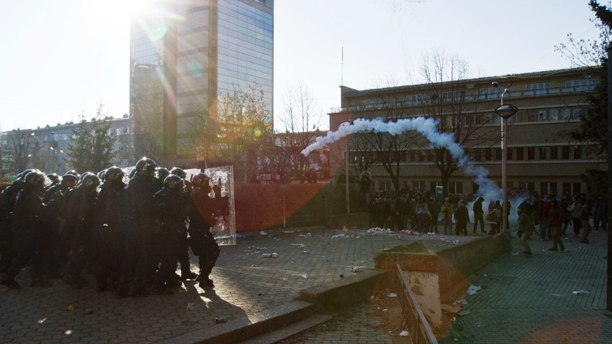 Protesters throws back a  tear gas canister at Kosovo police officers preventing students from storming the building of the main public Pristina University on Friday, Feb. 7, 2014. Hundreds of protesters are trying to break through a police cordon and reach offices of the dean of the public university who protesters say faked his teaching credentials(AP Photo/Visar Kryeziu)
